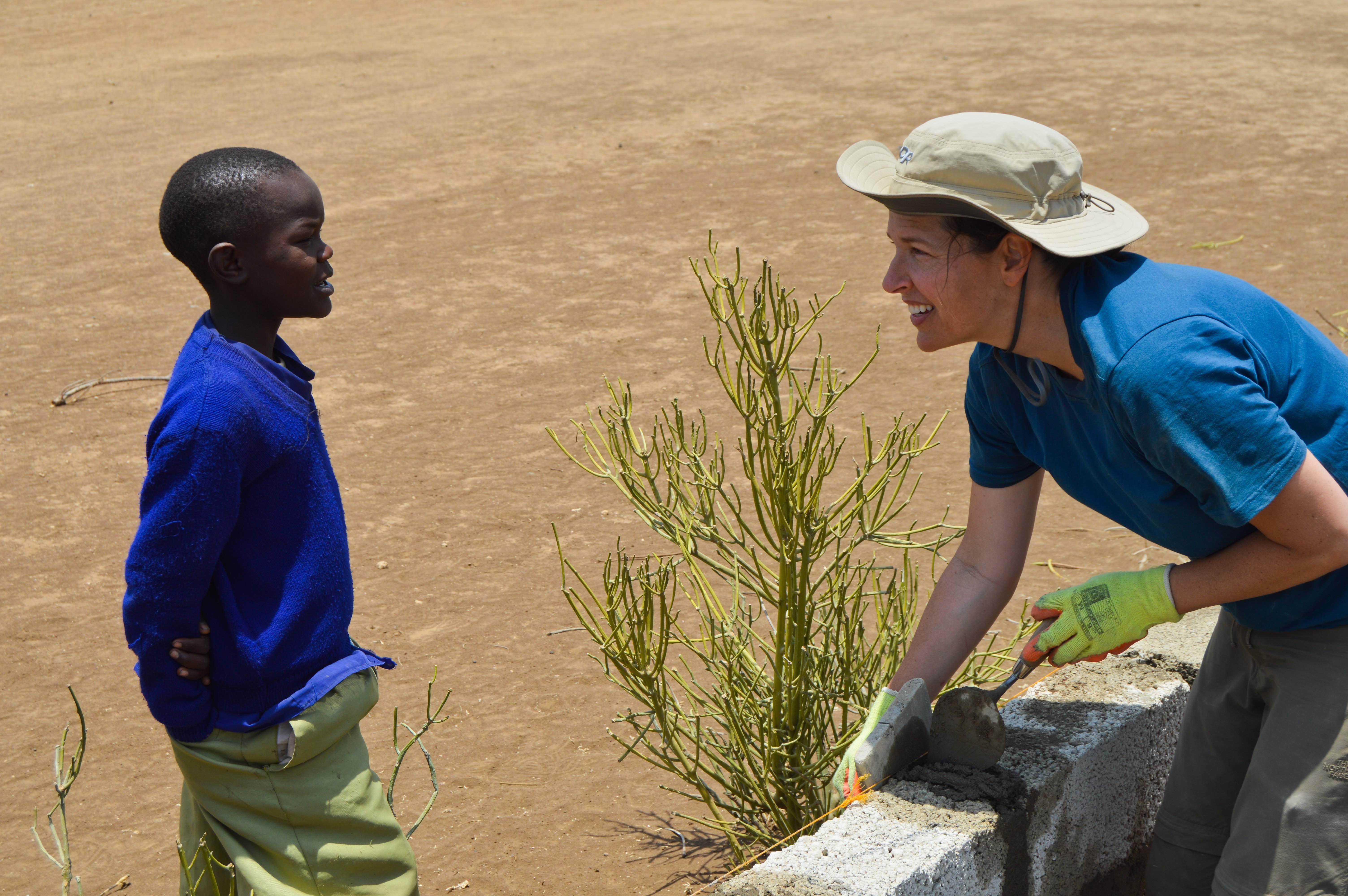 A teenage volunteer doing construction work in Tanzania builds a wall while chatting to a young child.
